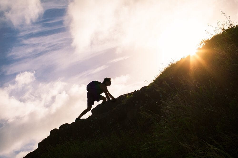 A man is climbing the hill to achieve his goal